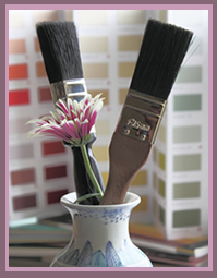 paint brushes and colour charts with flower vase